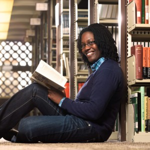Keisha sits at the base of library shelf stacks. Her back is against the side of the shelf and she holds M. Scott Peck's book The Different Drum. She looks at the camera, smiling.