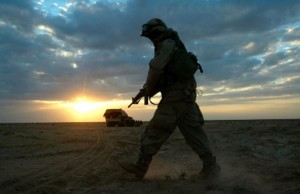 The sun rises in the background as a US soldier in fatigues walks across a dusty desert foreground. His rifle is pointed downward.