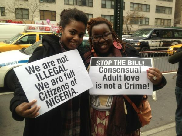 "Nigerians protesting outside their embassy in NY. Pictured: two young adult women holding signs: ""We are not ILLEGAL. We are full Citizens of Nigeria."" and ""STOP THE BILL! Consensual Adult love is not a Crime!"
