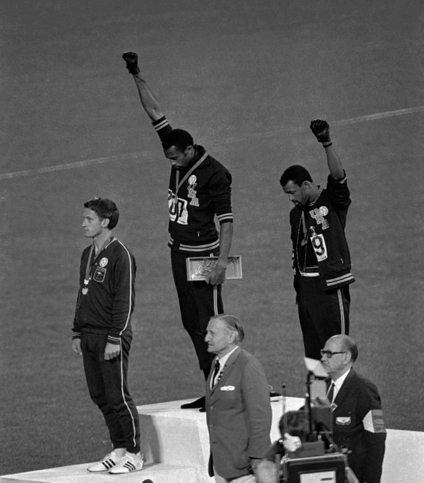 Three medalists standing on the winners' dais. Left, a White Australian, center and right, two black Americans. The Americans each have their fists high in the air. Two white officials stand below them.