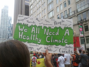 "A green and white hand-lettered sign reads ""We all need a healthy climate."" The word ""People"" and the names of non-human species surround this text."