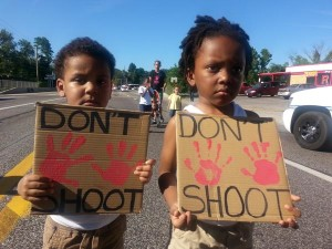 "Two children hold ""Hands Up Don't Shoot"" protest signs in Ferguson, MO"