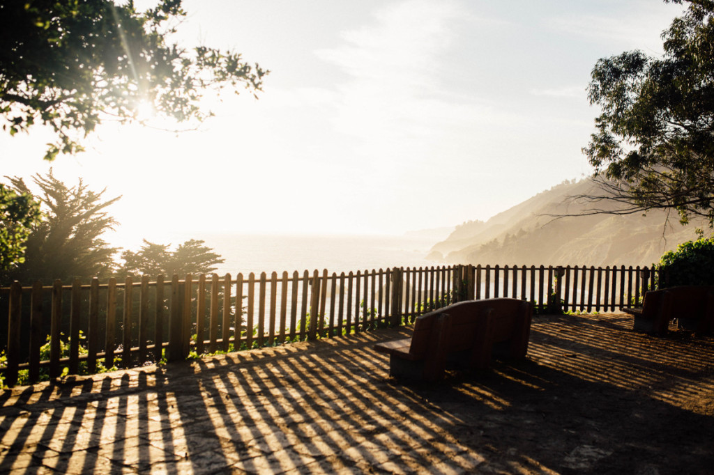 Photo overlooks a shoreline. The sky bright-lit by the sun, very light blue with large soft white clouds. In the foreground, with long shadows, a waist-high wooden fence stands across the middle of the view. To the right is an empty stone bench.