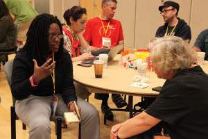 Keisha sits on the edge of her chair mid-conversation with Barb Siegel, illustrator. Barb is facing away from the camera. Photo via Sunlight Foundation Flickr stream.