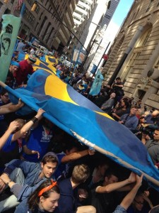 Hundreds of protesters sit under a large painted banner on Wall Street. 9/23. Photo credit: Yotam Maron (Twitter)