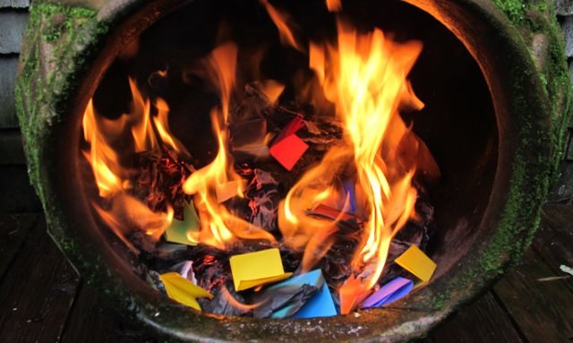 A bowl lies on its side, open top pointing toward us. Tiny colored folded papers are aflame inside.