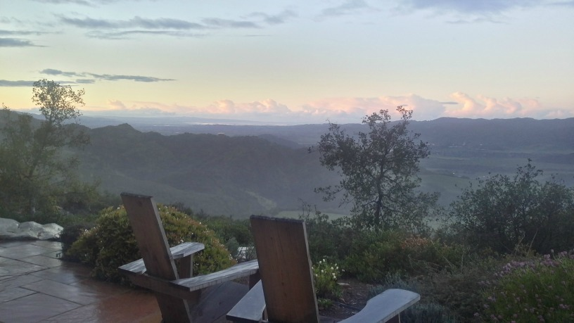 A photograph overlooking the Napa Valley near sunrise. In the foreground are two wooden chairs. They and the stone-tiled ground are wet from morning rain. In the distance, the hills are still dark and the clouds are tinged with red. There are sparse desert shrubs to the right and across the valley.