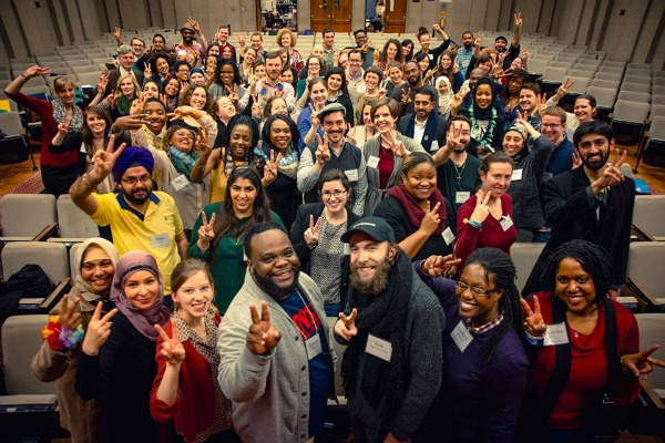 "A group photo of the attendees of the 2016 DC Interfaith Leadership Summit. Keisha is in the first row, toward the bottom right. Everyone is smiling and holding up two fingers in the hand gesture for ""peace."""