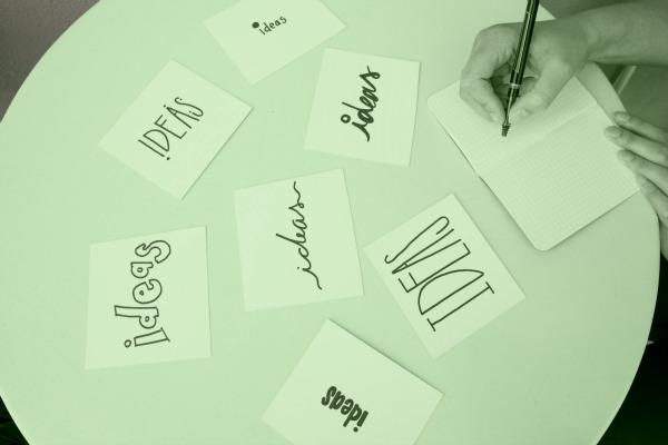 """A person writes """"Ideas"""" in different script styles. Only their hand is visible in the top right corner of the photo."""