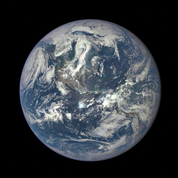 A NASA color image of Earth from space: the Americas are visible under wispy white clouds. The background is deep black.