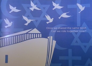 "Image: Eight white doves fly over a stylized white ark, all on a blue background with the cross, crescent, and star of Christianity, Islam, and Judaism, in the background. Text: ""Once we shared the same boat. Can we ride together now?"""