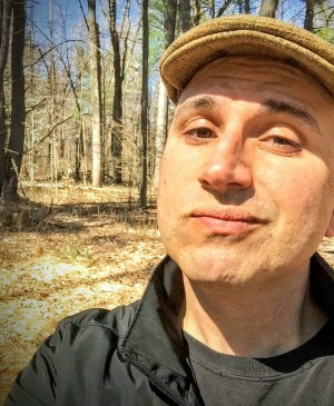 A candid photo of Peterson Toscano's head and shoulders. He is looking into the camera and grimacing slightly. In the background to his right, are trees: he appears to be in a forest. The branches are bare and the sky is blue.